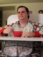 Stanley Thornton has his meal from his personalized high-chair with baby bib and pajamas on.