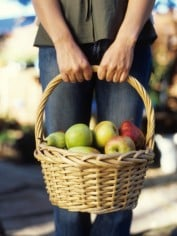 Woman holding basket of apples and pears