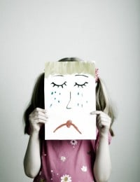 Girl holding up a sad face image.