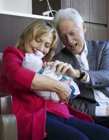 Bill and Hillary Clinton holding Chelsea