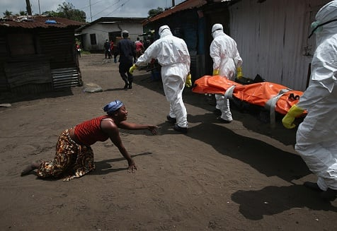 A woman crawls towards the body of her sister as Ebola burial team members take her sister Mekie Nagbe, 28, for cremation on October 10, 2014 in Monrovia, Liberia. (Photo: John Moore/Getty Images)