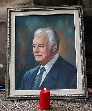 A candle is lit next to a portrait of Whitlam. (Photo by Daniel Munoz/Getty Images)