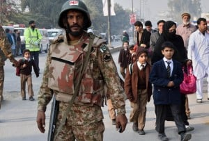 A Pakistani soldier stands guard as parents leave with their children near the site of an attack by Taliban gunmen on a school in Peshawar, on December 16, 2014 (AFP Photo:A Majeed)