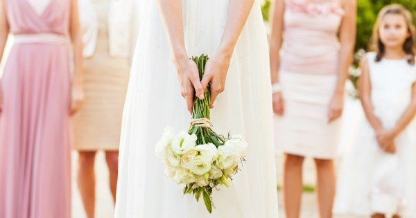 Midsection of bride holding flower bouquet with bridesmaid and flower girl standing in background. Horizontal shot.
