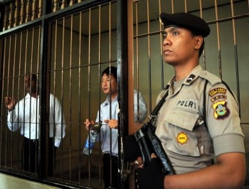 An Indonesian policeman stands guard next to a detention room where Australians Myuran Sukumaran (L) and Andrew Chan (C), members of the so called Bali Nine gang, wait for their trial in Denpasar on the island of Bali on October 8, 2010. An Indonesian prison chief testified on October 8, that two Australian drug smugglers on death row have given great contribution in teaching fellow inmates and should not be executed. Andrew Chan and Myuran Sukumaran, members of the so-called Bali Nine gang, are seeking 20 years to life in prison for a 2005 attempt to smuggle 8.3 kilograms (18 pounds five ounces) of heroin into Australia from Bali island. AFP PHOTO / SONNY TUMBELAKA (Photo credit should read SONNY TUMBELAKA/AFP/Getty Images)