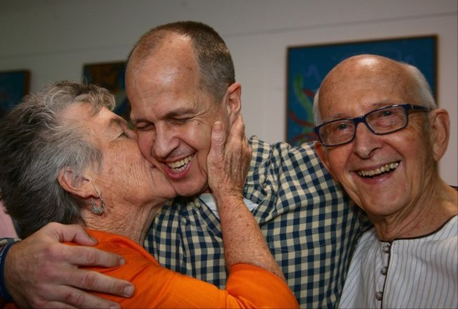 Peter Greste is kissed by his mother Lois (L) and father Juris (R) upon his arrival at Brisbane's international airport in the early hours of February 5, 2015. (Photo: PATRICK HAMILTON/AFP/Getty Images)