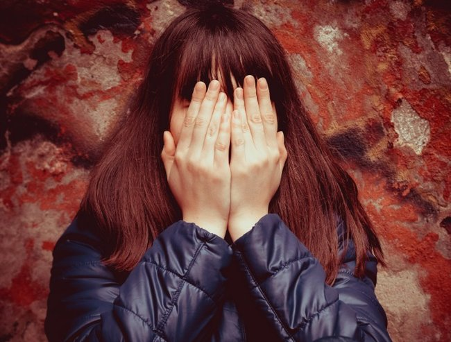teenager girl with hands over eyes near dramatic red wall outdoors
