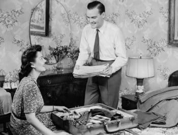 Woman assisting man packing suitcase (B&W)