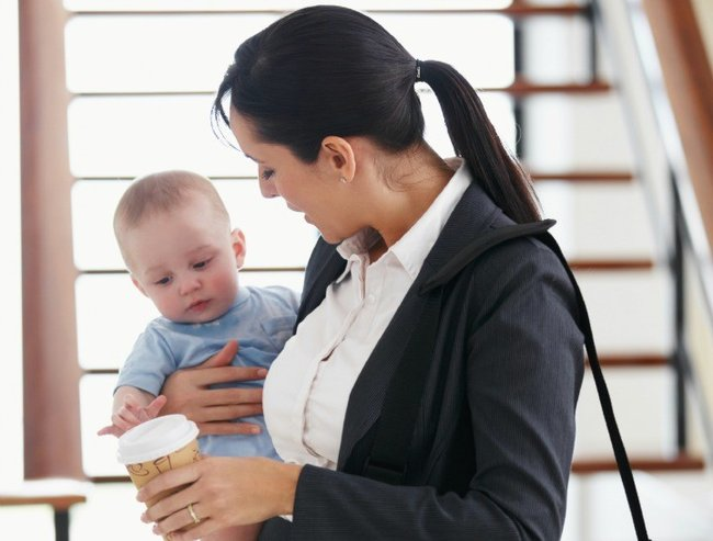Working mother standing with her briefcase holding a baby