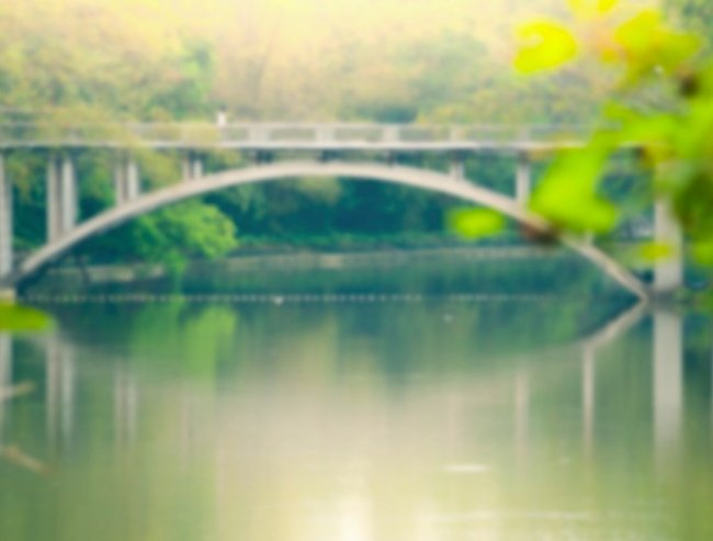 Blur background image of arc stone bridge across the lake in summer sunlight.