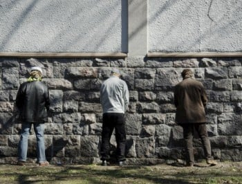 men urinating against wall