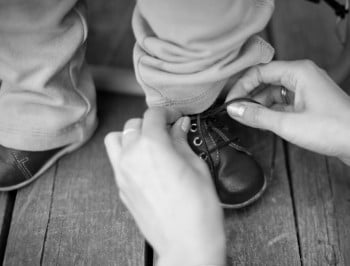 A parent is tying a shoe of a child