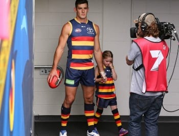 A buff footballer comforting a cute crying child...shameless swoon.