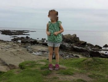 The latest ghost photobomber is standing right behind a little girl.