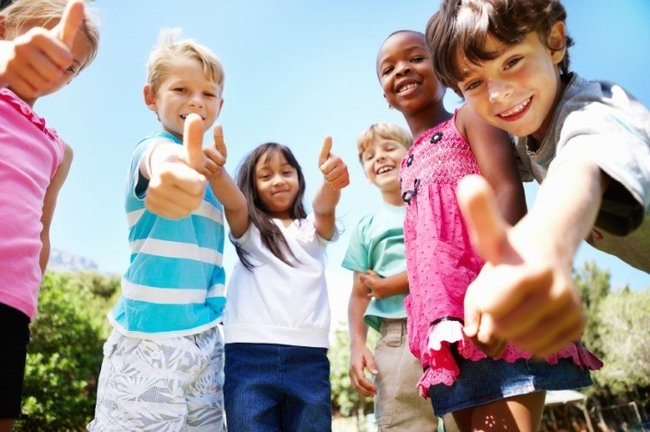 Low angle view of cute kids standing outdoors and giving thumbs up