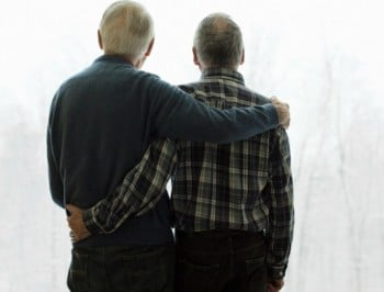 Rear view of a gay senior couple looking out at winter together.