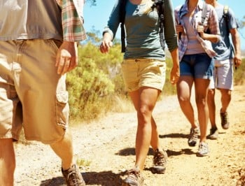 Four attractive young hikers walking down a dirt road while smiling