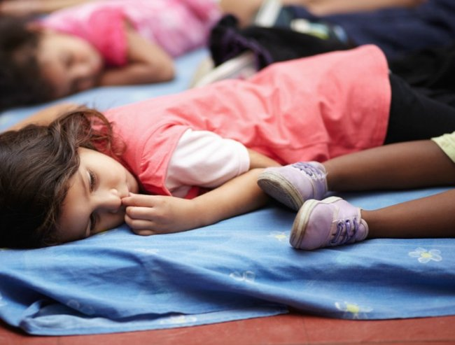 Preschool children all lying down and getting ready to nap