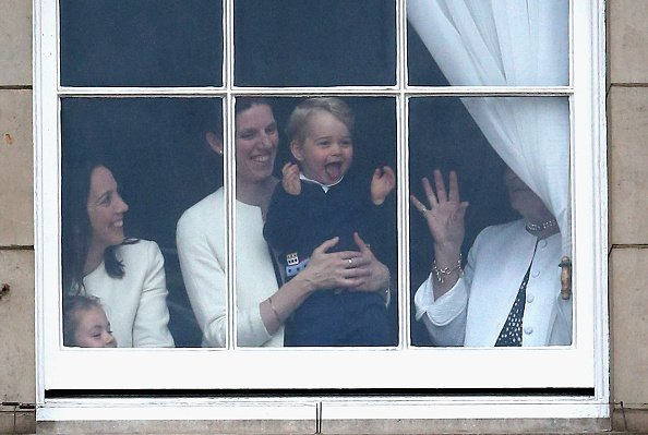 LONDON, ENGLAND - JUNE 13:  Prince George of Cambridge is held by his nanny Maria Teresa Turrion Borrallo as he waves from the window of Buckingham Palace as he watches the Trooping Tthe Colour on June 13, 2015 in London, England. . The ceremony is Queen Elizabeth II's annual birthday parade and dates back to the time of Charles II in the 17th Century when the Colours of a regiment were used as a rallying point in battle.  (Photo by Chris Jackson/Getty Images)