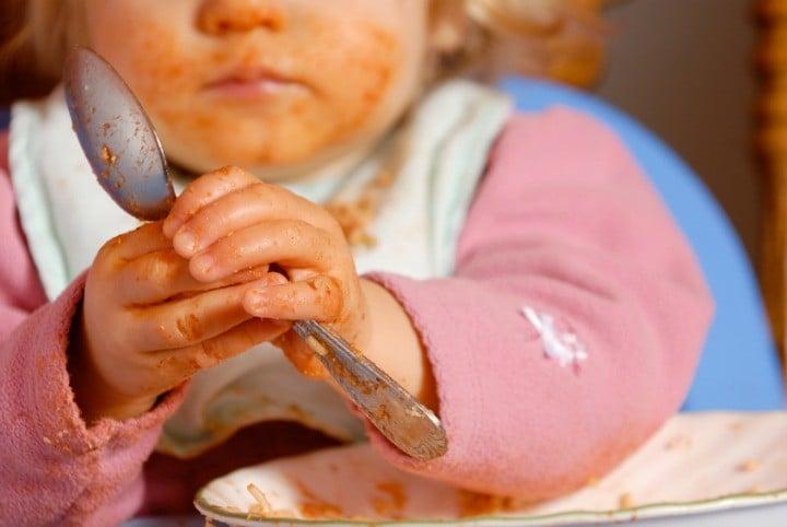 Messy baby eats spaghetti
