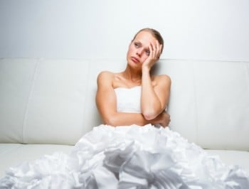 Sad bride crying sitting on a sofa, smitten, pondering, feeling low and depressed