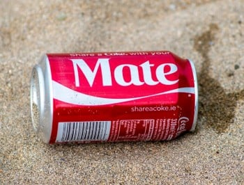 coca cola can washed up on sandy beach with the name mate printed on it