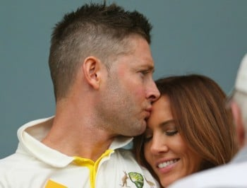 ADELAIDE, AUSTRALIA - DECEMBER 10:  Michael Clarke of Australia kisses his wife Kyly Clarke as he waits during a rain delay during day two of the First Test match between Australia and India at Adelaide Oval on December 10, 2014 in Adelaide, Australia.  (Photo by Scott Barbour/Getty Images)