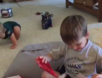 Little kid gets truly crappy present. Handles it well.