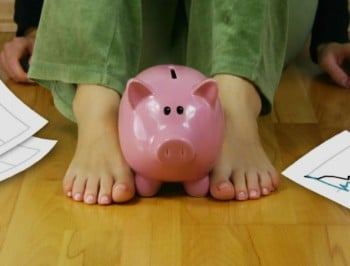 Upset woman sitting on an empty floor, holding a piggy bank and a paper with interest