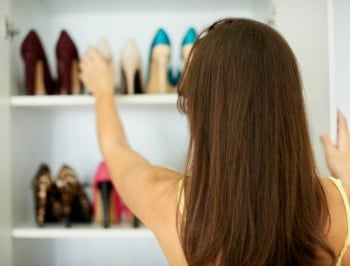 Rearview of a woman reaching for a pair of shoes in her closet