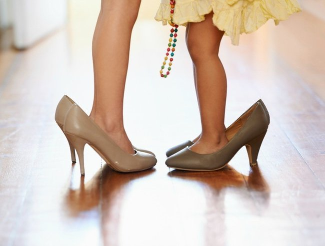 Cropped shot of two little girls wearing over-sized high heels