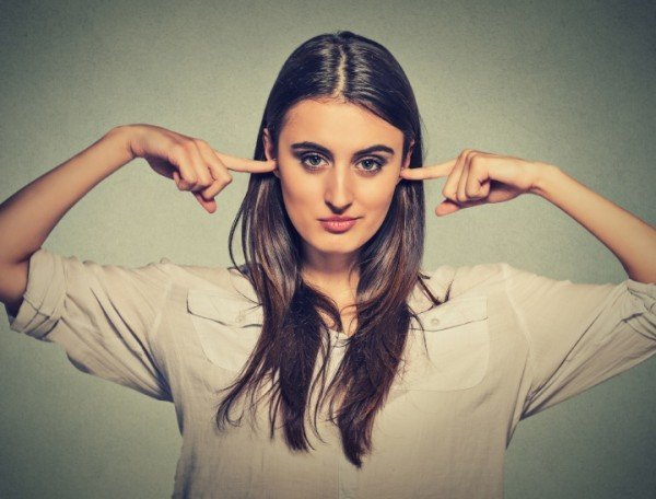 Woman plugging ears with fingers doesn't want to listen