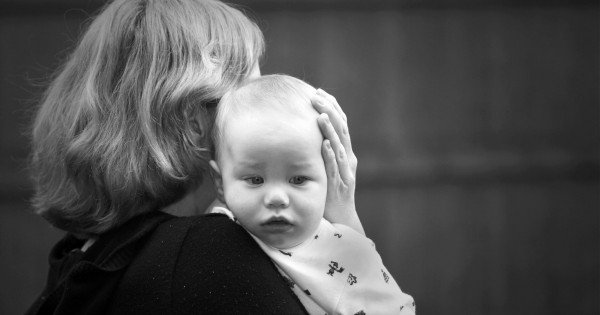 Mother comforting a sad baby in black and white