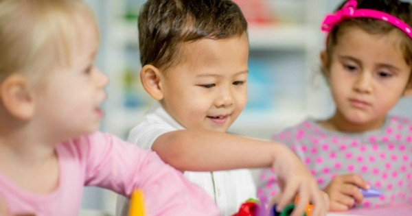 A multi-ethnic group of elementary age children are playing with stackable toys in school at their desk.