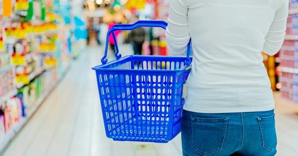 woman holding a basket in supermarket.