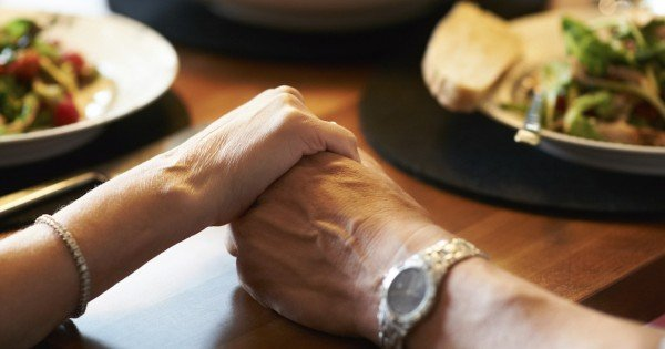 Closeup cropped image of a couple holding hands across a table filled with food