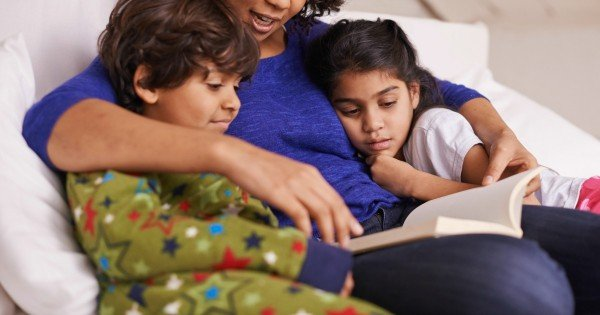 A young mother reading to her children while relaxing at home