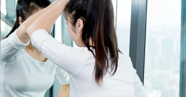 Young asian woman thinking in the mirror.