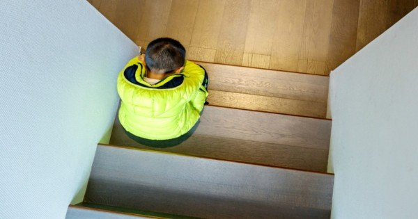 Little boy sitting on a staircase, looks lonely.