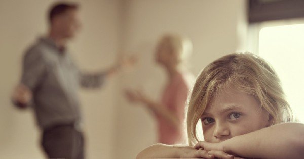 Shot of a little girl looking unhappy as her parents argue in the background