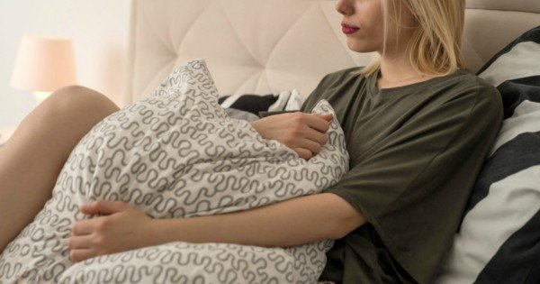Pensive woman feeling lonely while relaxing in bedroom.