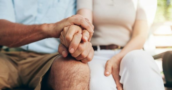 Couple who are considering retirement holding hands.