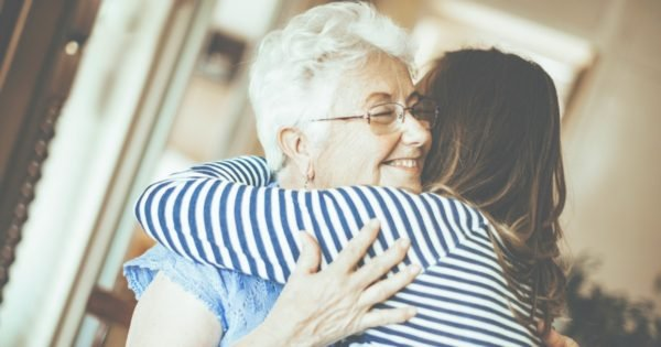 Elderly lady who is going into retirement hugging her daughter.