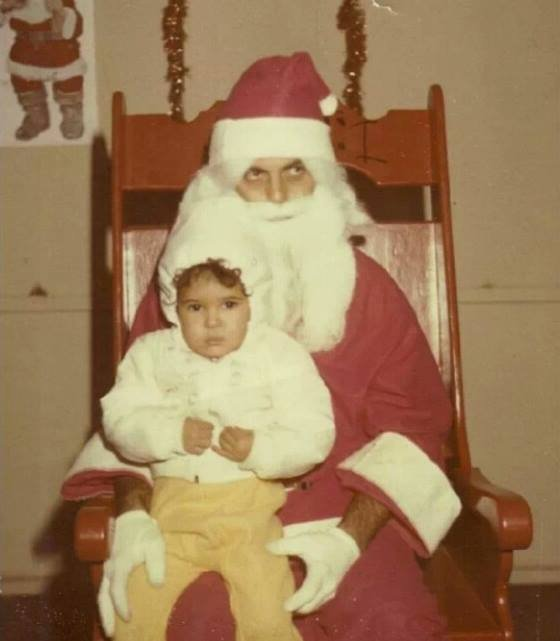 The child and Santa look equally glad to be together.