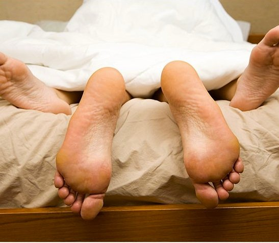 couple having sex with feet poking out of covers