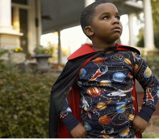 boy pretending to be a superhero and wearing a cape.