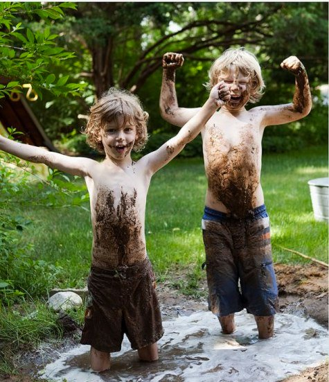 two boys with arms raised playing in mud