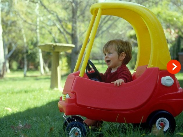 little boy playing in toy car and smiling