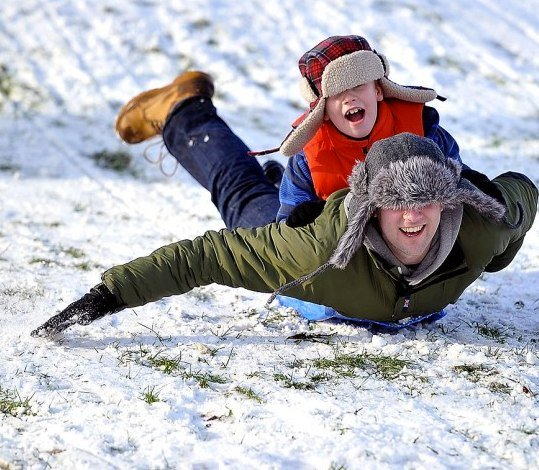 father and son sliding down a snowy hill