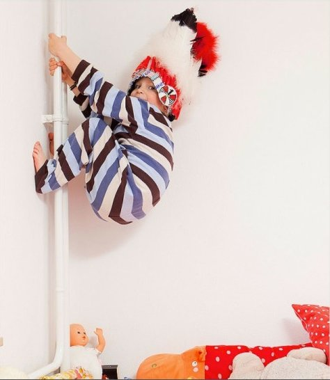 boy climbing up a pole in his pyjamas